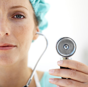 Female Doctor Wearing Protective Headgear and Using Stethoscope